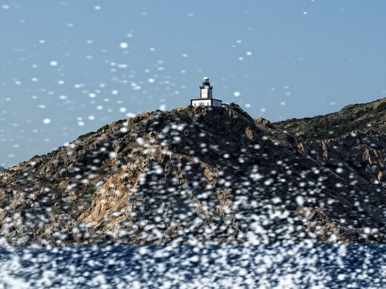 Lighthouse scene through Boston Whaler spray, near Calvi