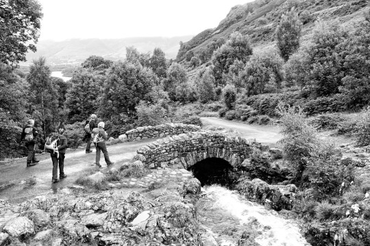 Hikers leaving on a walk over old stone bridge black and white photo, The Lake District England